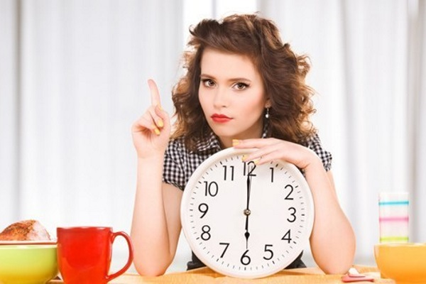 brunette-holding-a-clock-and-waiting-to-eat