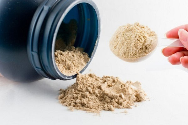 hand-holding-scoop-of-whey-protein-powder