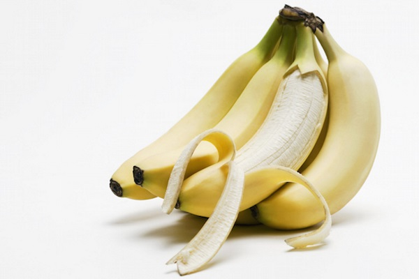 One peeled banana in bunch