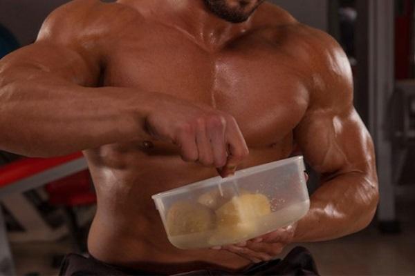 Buff dude eating in gym FLEX