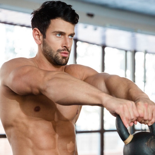 Portrait of a muscular man workout with kettle ball in fitness gym