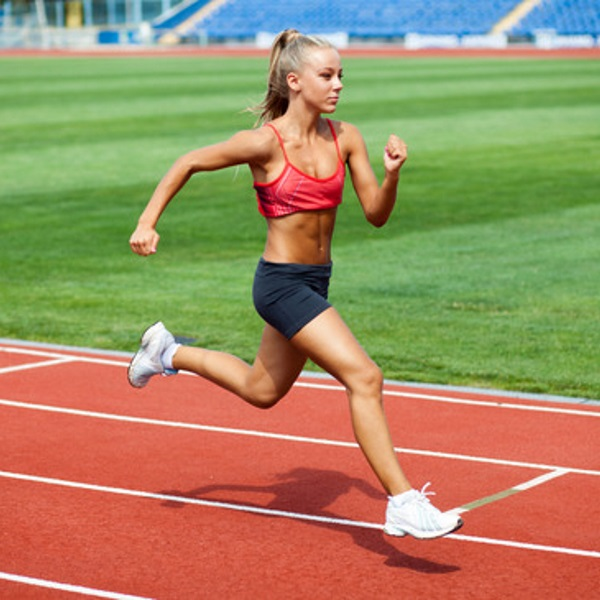 Attractive young woman in a sports suit running on a treadmill at the stadium