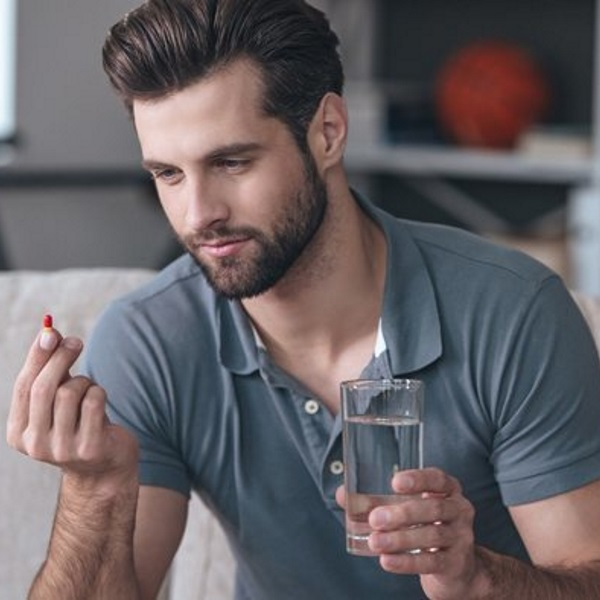 young-man-with-pill-and-glass-of-water-in-hand