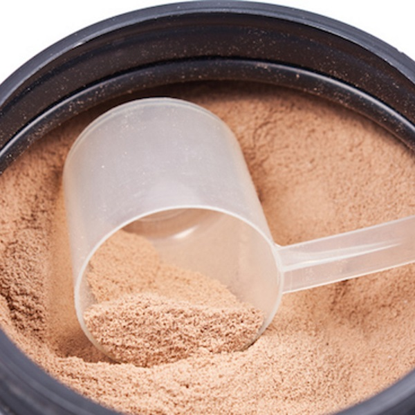 Scoop of chocolate whey isolate protein in black plastic containter on white background