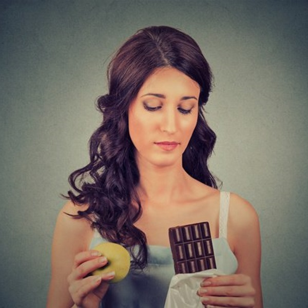 brunette-holding-apple-and-dark-chocolate-wondering-which-to-eat