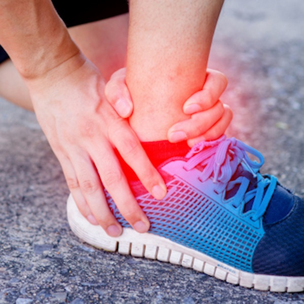 Runner touching painful twisted or broken ankle. Runner training accident